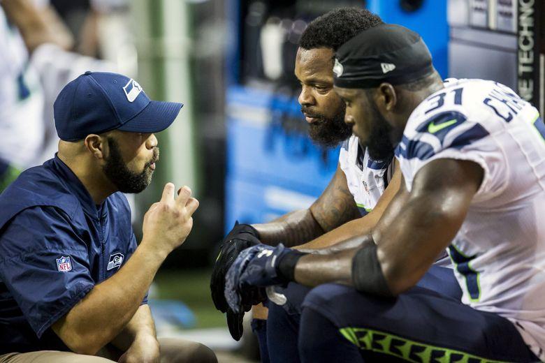 Seahawks defensive coordinator Kris Richard talks to defensive end Michael Bennett and safety Kam Chancellor. (Bettina Hansen / The Seattle Times)