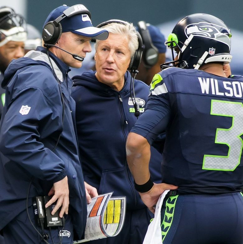 Seahawks offensive coordinator Darrell Bevell, coach Pete Carroll and quarterback Russell Wilson talk during a 2015 game against the Carolina Panthers at CenturyLink Field in Seattle . (Bettina Hansen/The Seattle Times)