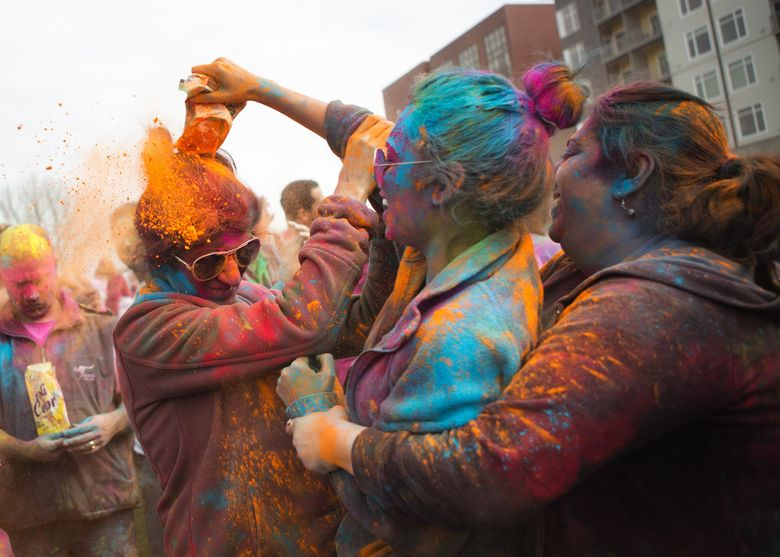 Geetanjali Sachdeva, left, has a packet of powder dumped on her by cousin Priyanka Dhawan as Pratima Sachdeva, right, looks on during a Holi celebration at Downtown Park in Redmond in 2016.(Lindsey Wasson / The Seattle Times)