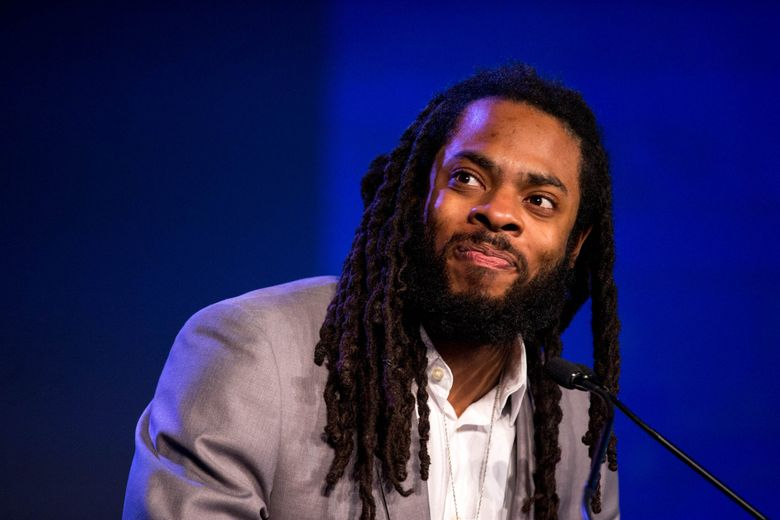 Richard Sherman introduces John Clayton during the Seattle Sports Star awards at the Sheraton Seattle Hotel on Thursday, Feb. 8, 2018. The event celebrated the achievements of Washington sports with a reception and award show.  (Courtney Pedroza / The Seattle Times)