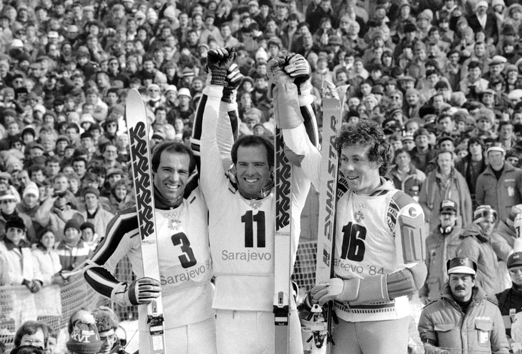 Phil Mahre is flanked by his twin brother Steve, left, and French skier Didier Bouvet in the podium on Mt. Bjelasnica, on Sunday, Feb. 19, 1984 in Sarajevo after the men's special slalom event, the last alpine competition on the last day of the XIV Winter Olympic Games. Phil won the gold medal, Steve placed second winning silver and Bouvet claimed bronze. (AP Photo/KS) (KS/AP)