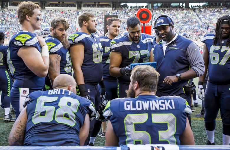 Former offensive lineman and current offensive assistant Lemuel Jeanpierre talks with the offensive line on the bench. (Bettina Hansen / The Seattle Times)