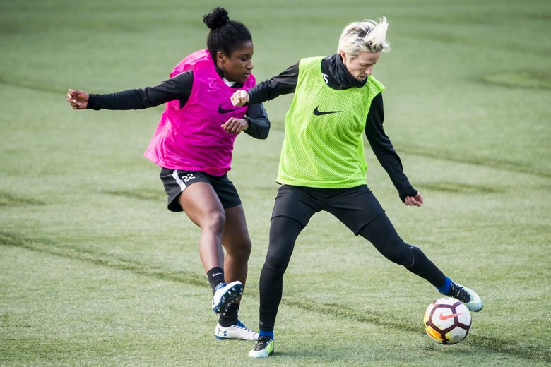 Forwards Jasmyne Spencer, left and Megan Rapinoe fight for possession as Seattle Reign FC practice at Memorial Stadium in Seattle Monday. (Bettina Hansen/The Seattle Times)