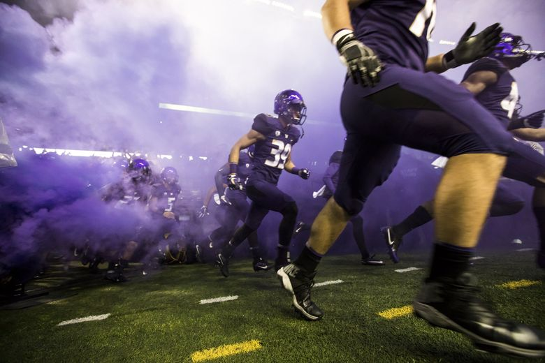 Players are introduced amid a cloud of purple smoke as the University of Washington Huskies take on the California Golden Bears at Husky Stadium in Seattle Saturday October 7, 2017. (Bettina Hansen / The Seattle Times)