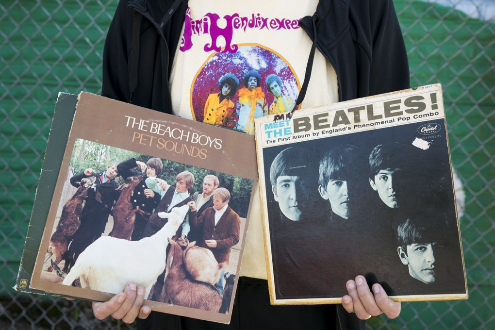 Dan Hughes, tasked with taking the Storm to the next level, shows off two of his favorite records by The Beach Boys and The Beatles while wearing his Jimi Hendrix t-shirt at Daybreak Records in the Fremont neighborhood. (Bettina Hansen/The Seattle Times)