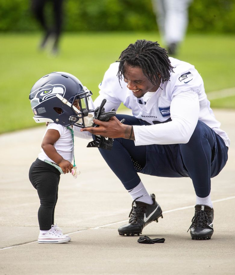 Seahawks cornerback Tre Flowers puts his helmet on 1-year old daughter Bailee at the end of camp in May.   Flowers has started five games for the Seahawks in his rookie campaign. (Dean Rutz / The Seattle Times)
