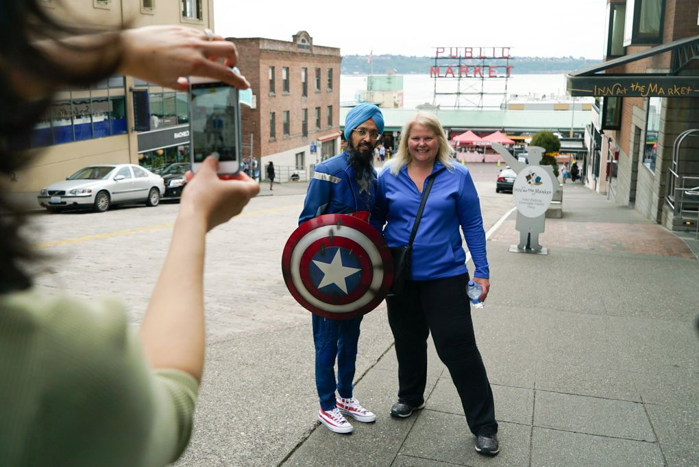 Vishavjit Singh poses for a photo with Katie Zunich, a tourist from San Diego, in front of Pike Place Market. (Corinne Chin / The Seattle Times)