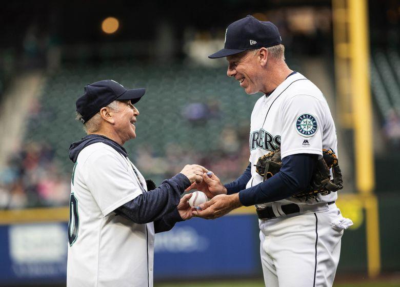 Paul Simon autographs his first pitch for Mariners third base coach Scott Brosius Thursday.   (Dean Rutz / The Seattle Times)