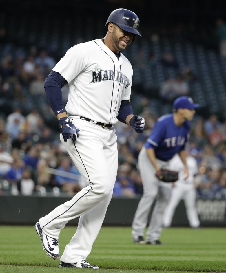 Seattle Mariners' Nelson Cruz, left, limps toward first base after being hit by a pitch from Texas Rangers' Brandon Mann, right, on the foot in a baseball game Tuesday, May 15, 2018, in Seattle. (Elaine Thompson / The Associated Press)