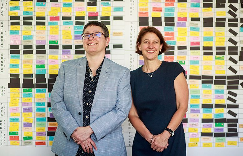 Beth Barrett, SIFF artistic director, left, and Sarah Wilke, SIFF executive director, stand in front of the enormous corkboard that is SIFF's master schedule.  (Erika Schultz/The Seattle Times)
