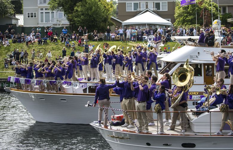 Even the Husky Band, performing from the decks of three boats last year, turns out for the traditional opening day of boating season and Windermere Cup rowing event.  (Bettina Hansen/The Seattle Times, 2018)