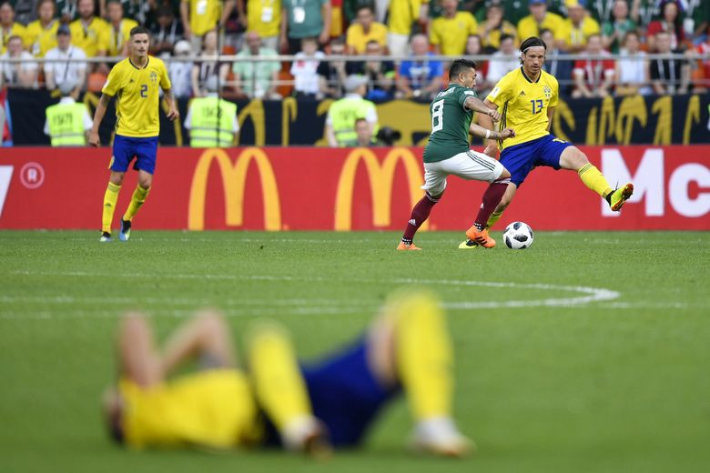 Sweden's Gustav Svensson, top right, challenge for the ball with Mexico's Marco Fabian as Sweden's Marcus Berg lays on the pitch during the group F match between Mexico and Sweden.(Martin Meissner / The Associated Press)