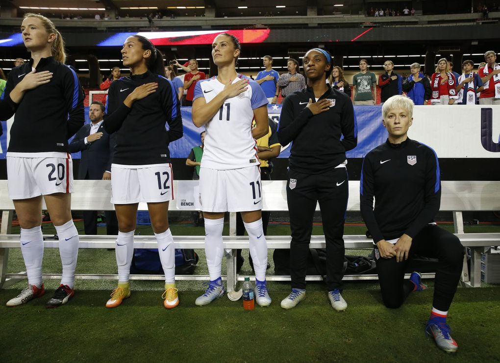 USA's Megan Rapinoe, right, kneels next to teammates as the national anthem is played before a soccer match in September 2016. (AP Photo/John Bazemore, file)