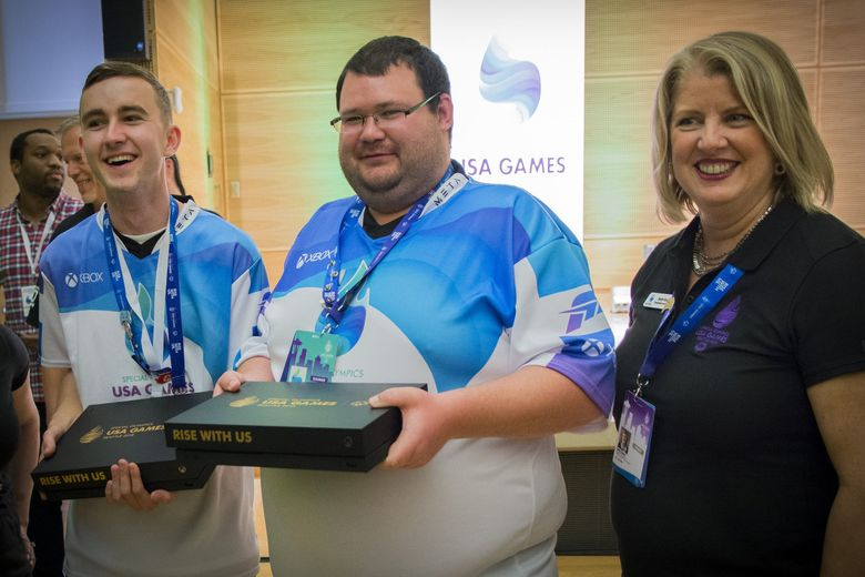 Nicholas Rasmussen, left, and Timothy Dempsey, center, celebrate with Special Olympics USA CEO Beth Knox after winning the Xbox tournament at the Games.  (Xbox / )