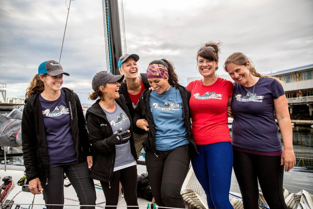 """From Left: Haley Lhamon, Anna Stevens, Aimee Fulwell (back), Jeanne Goussev, Allison Dvaladze, and Kelly Danielson laugh while wearing their """"Sail Like a Girl"""" team shirts in the Bell Harbor Marina on July 9. They are six members of the eight-woman team that recently won a boat race from Port  Townsend to Ketchikan, Alaska.  (Rebekah Welch / The Seattle Times)"""