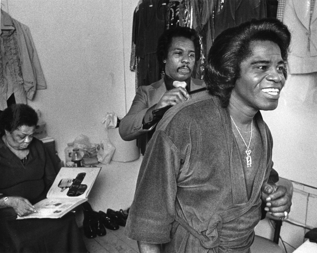 James Brown has his hair attended to by Henry Stall,  his hairstylist and personal manager, as his wardrobe coordinator Gertrude Sanders waits in the background. He was primping by a mirror in his dressing room between shows at the Showbox in 1980. (Matt McVay / The Seattle Times)