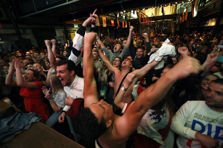 English, Russian and other fans react as England defeats Colombia on penalties in their round of 16 match. (Rebecca Blackwell / The Associated Press)