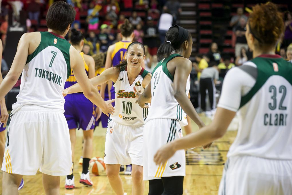 Storm guard Sue Bird fives her teammates, from left, Ramu Tokashiki, Jewell Loyd and Alysha Clark, after the Seattle Storm defeated the Los Angeles Sparks 68-61 at Key Arena in Seattle, Wednesday July 15, 2015.  (Bettina Hansen / The Seattle Times)