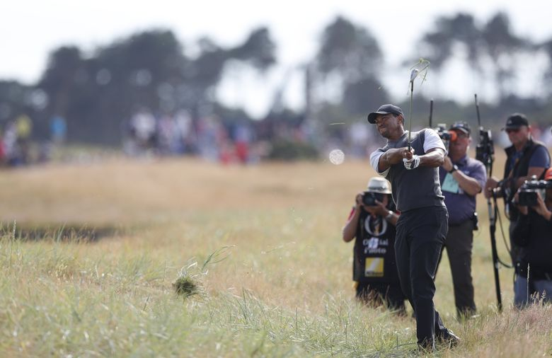 Tiger Woods of the US plays out of the rough on the 18th hole during the third round of the British Open. (Alastair Grant / The Associated Press)