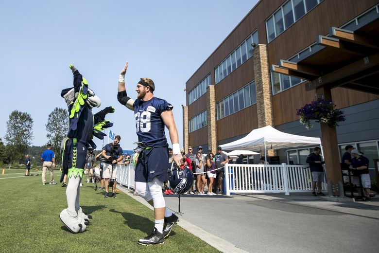 Seahawks tight end Will Dissly high-fives mascot Blitz at Seattle Seahawks Training Camp at the Virginia Mason Athletic Center in Renton Monday. (Bettina Hansen / The Seattle Times)