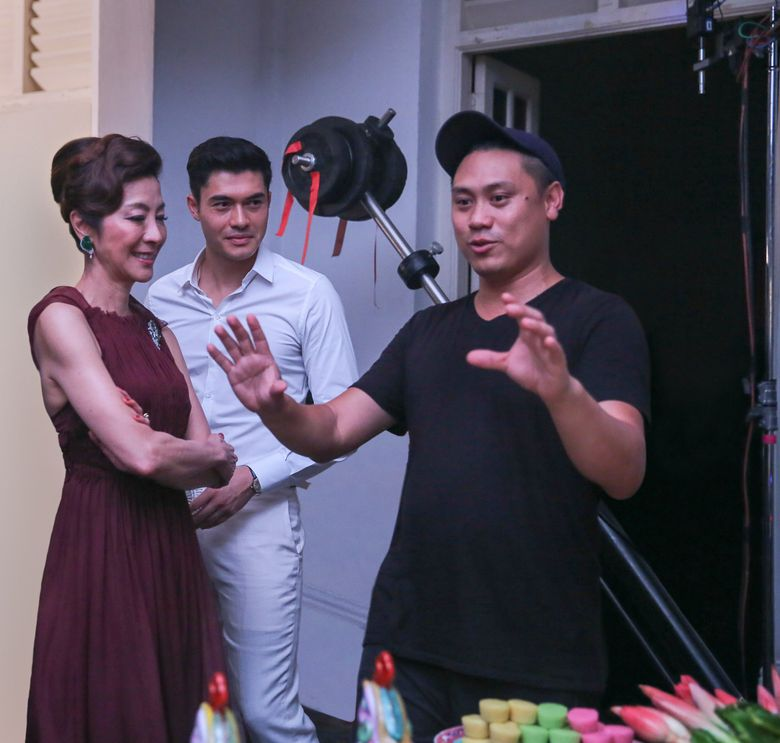 """Michelle Yeoh, Henry Golding, center, and director Jon M. Chu on the set of """"Crazy Rich Asians.""""(Sanja Bucko)"""