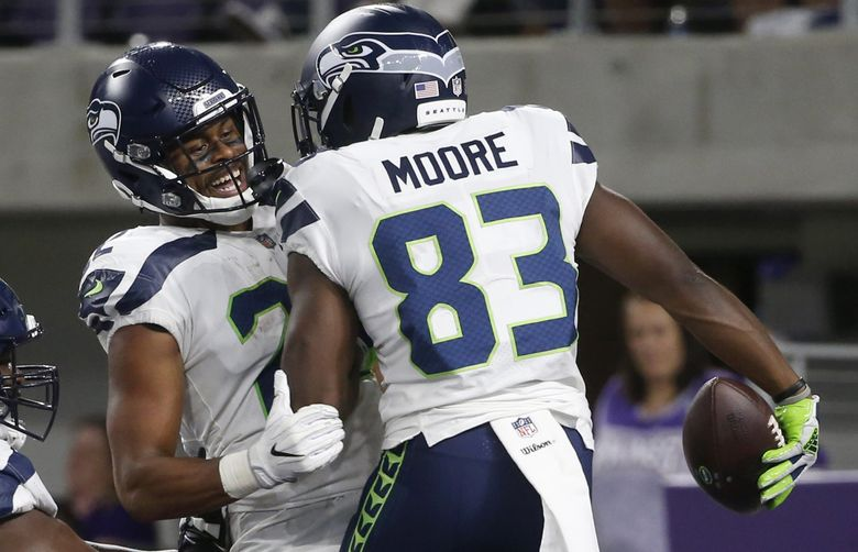 Seattle Seahawks wide receiver David Moore (83) celebrates with teammate C.J. Prosise after catching a 36-yard touchdown pass.  (Bruce Kluckhohn / The Associated Press)