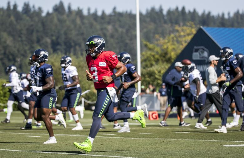 The Seahawks, led by quarterback Russell WIlson, take the field for training camp at the Virginia Mason Athletic Center. (Bettina Hansen / The Seattle Times)
