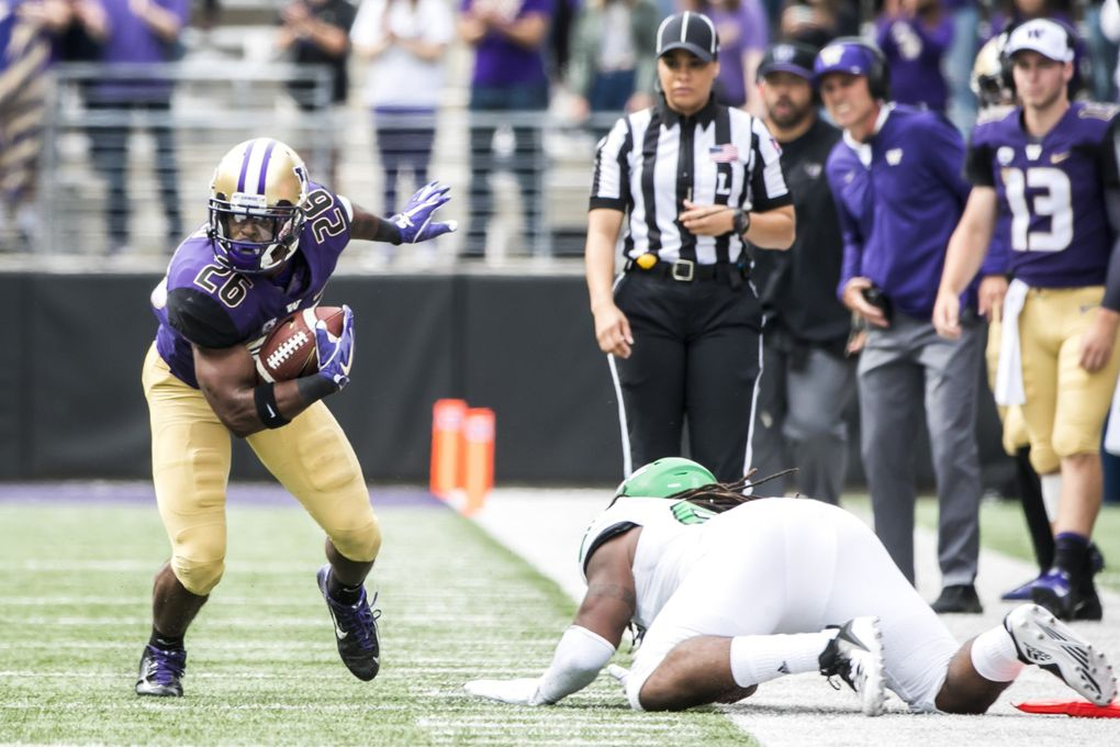 Huskies running back Salvon Ahmed picks up 12 yards and a first down, ditching Fighting Hawks linebacker Everett Williams in the first quarter, as the University of Washington Huskies take on the North Dakota Fighting Hawks for their home opener at Husky Stadium in Seattle Saturday September 8, 2018.  (Bettina Hansen / The Seattle Times)