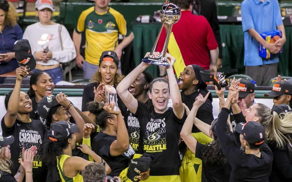Storm forward Breanna Stewart lifts the trophy with her teammates after the Seattle Storm swept the Washington Mystics to win the WNBA title at EagleBank Arena in Fairfax, Virginia on Wednesday night. (Bettina Hansen / The Seattle Times)