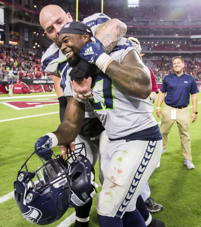 Seahawks center Justin Britt puts Seahawks running back Mike Davis in a headlock as they walk off the field in celebration after the Seattle Seahawks defeated the Arizona Cardinals 20-17 at State Farm Stadium in Glendale, Arizona Sunday September 30, 2018. Davis rushed for 101 yards on 21 carries and two touchdowns.   (Bettina Hansen / The Seattle Times)