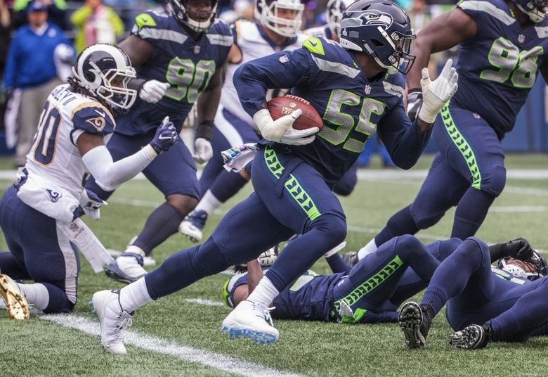 Seattle Seahawks defensive end Frank Clark (55) intercepts the ball at the goal line during first quarter action as the Seattle Seahawks play the Los Angeles Rams at CenturyLink Field in Seattle on October 7, 2018. At left is Los Angeles Rams running back Todd Gurley (30).  208039 (Mike Siegel / The Seattle Times)