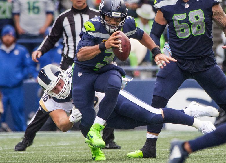 Seattle Seahawks quarterback Russell Wilson (3) scrambles during 2nd quarter action out of the grasp of Los Angeles Rams linebacker Matt Longacre (96) as the Seattle Seahawks play the Los Angeles Rams at CenturyLink Field in Seattle on October 7, 2018. (Mike Siegel / The Seattle Times)