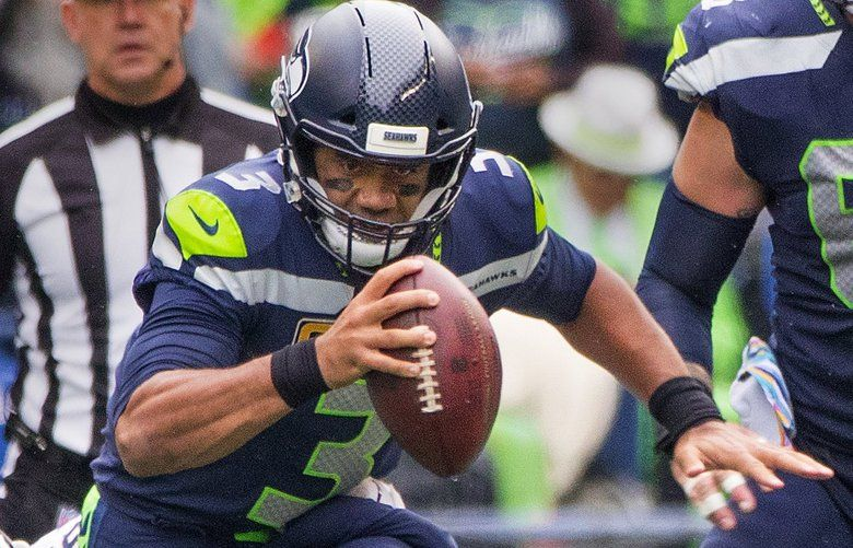 Seattle Seahawks quarterback Russell Wilson (3) scrambles during 2nd quarter action out of the grasp of Los Angeles Rams linebacker Matt Longacre (96) as the Seattle Seahawks play the Los Angeles Rams at CenturyLink Field in Seattle on October 7, 2018.  208039