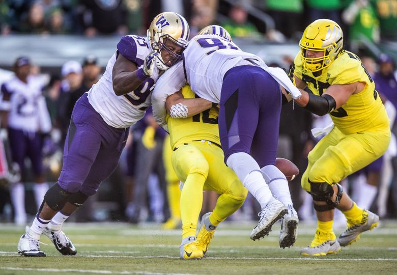 Washington's Jaylen Johnson lays a hit on Oregon quarterback Justin Herbert, resulting in a targeting penalty, and his ejection from the game in the fourth quarter. At left is Levi Onwuzurike, who nearly had Herbert with a clean sack. (Dean Rutz / The Seattle Times)