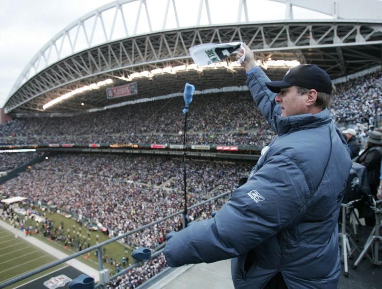 Paul Allen waves to the crowd after raising the 12th Man flag before the start of the NFC Championship Game at Qwest Field in 2006. The stadium was renamed CenturyLink Field in 2011 and will almost certainly stay that way through 2033 despite an online petition to rename it in Allen's honor. (Mike Siegel / The Seattle Times)