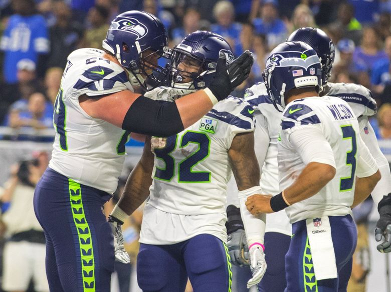 Seattle Seahawks offensive guard J.R. Sweezy (64) congratulates Seattle Seahawks running back Chris Carson (32) after Carson scores a 4th quarter touchdown as the Detroit Lions play the Seattle Seahawks at Ford Field in Detroit Michigan on October 28, 2018. (Mike Siegel / The Seattle Times)