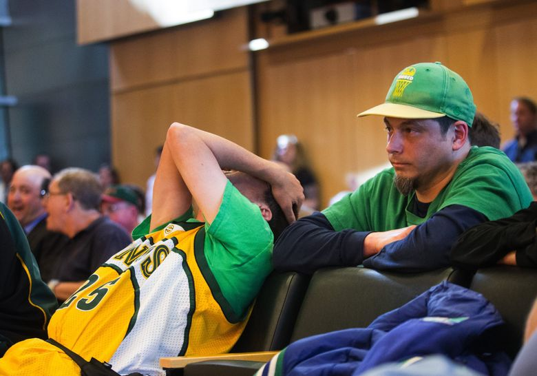 """Sonics fan Kenneth Knutsen, left, collapses in his seat while Jason Billingsley purses his lips as they hear council member M. Lorena Gonzalez deliver her deciding """"no"""" vote during a Seattle City Council meeting to vote on whether to vacate part of Occidental Avenue South at Seattle City Hall on Monday, May 2, 2016. The council decided on a 5-4 vote against the street vacation. A yes vote would have allowed entrepreneur Chris Hansen to move forward with plans to build an multi-sport arena.  (Lindsey Wasson / The Seattle Times)"""