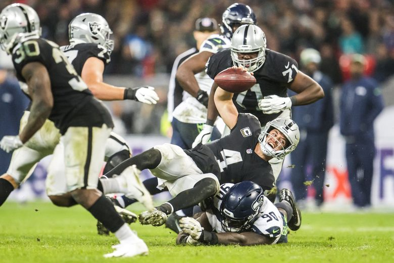 Raiders quarterback Derek Carr is sacked for a loss of one by Seahawks defensive tackle Jarran Reed as the Seattle Seahawks take on the Oakland Raiders Sunday October 14, 2018 at Wembley Stadium in London. Carr was clutching his left arm while walking off the field.  It was the sixth sack on Carr for the night. 208122 (Bettina Hansen / The Seattle Times)