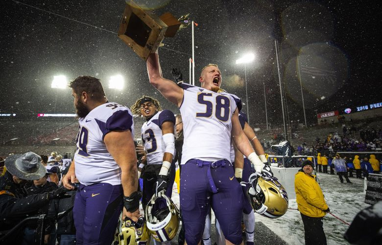 Kaleb McGary holds the Apple Cup trophy aloft after Washington defeated Washington State in Pullman on Nov. 24, 2018. (Dean Rutz / The Seattle Times)