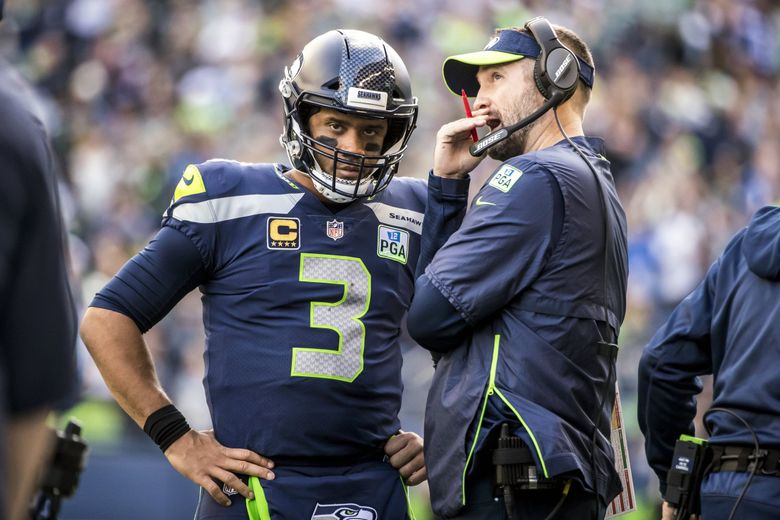 Seahawks quarterback Russell Wilson talks with offensive coordinator Brian Schottenheimer as the Seattle Seahawks take on the Los Angeles Chargers at CenturyLink Field in Seattle Sunday November 4, 2018. (Bettina Hansen / The Seattle Times)