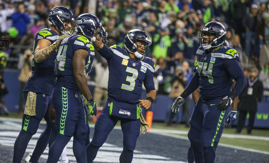 Seattle Seahawks quarterback Russell Wilson and Seattle Seahawks offensive tackle George Fant, right, celebrate Seattle Seahawks tight end Ed Dickson fourth quarter touchdown. (Mike Siegel / The Seattle Times)
