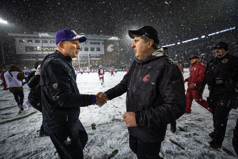 Chris Petersen and Mike Leach meet at midfield after the Apple Cup. (Dean Rutz / The Seattle Times)