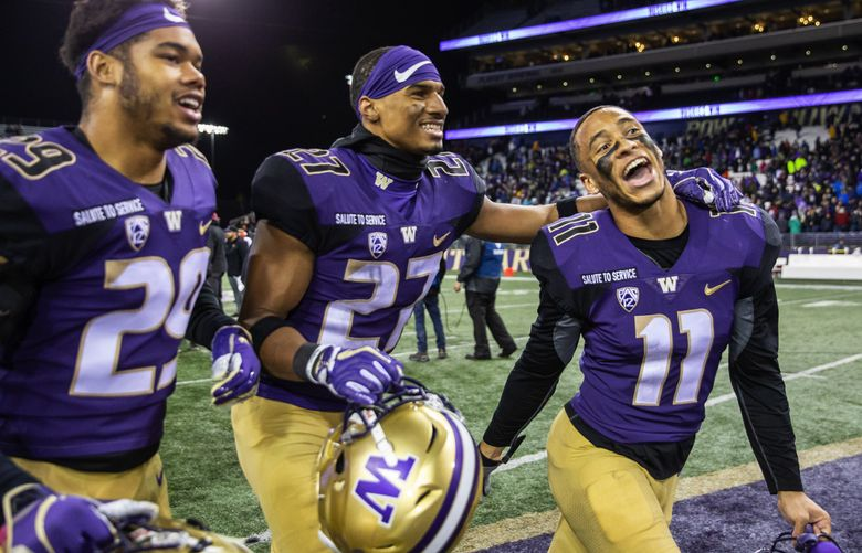 Washington defensive backs Keith Taylor (27) and Brandon McKinney run off the field, celebrating their win over Stanford. (Dean Rutz / The Seattle Times)