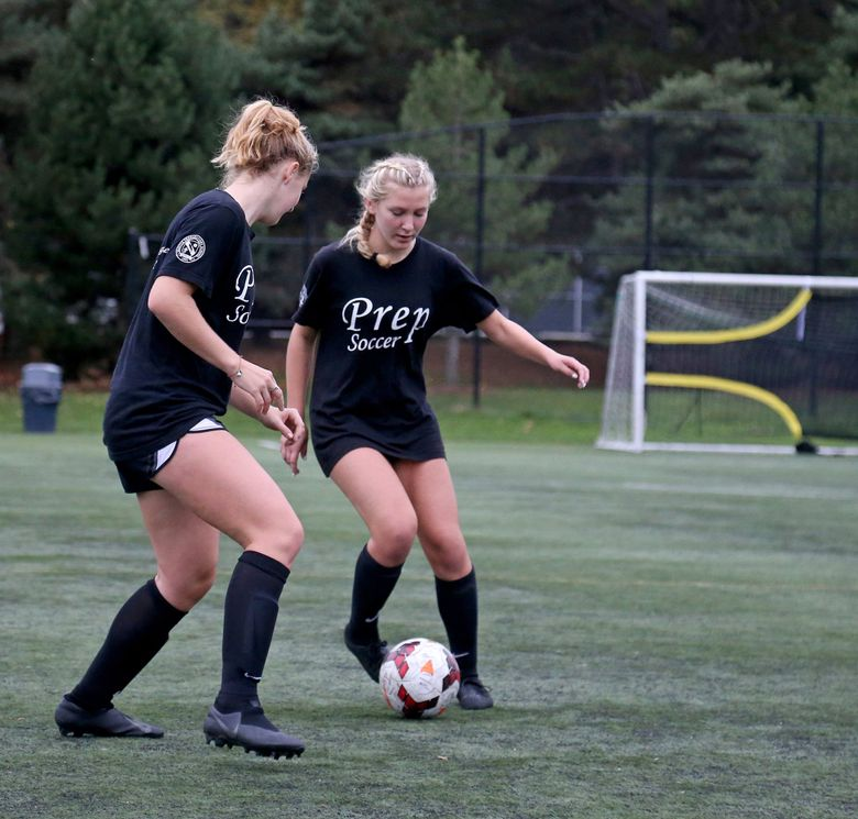 Seattle Prep freshman Jayce Woodward, right, works the ball against senior Bea Franklin, left. Both players decided they'd rather play high-school ball than academy soccer. (Greg Gilbert / The Seattle Times)
