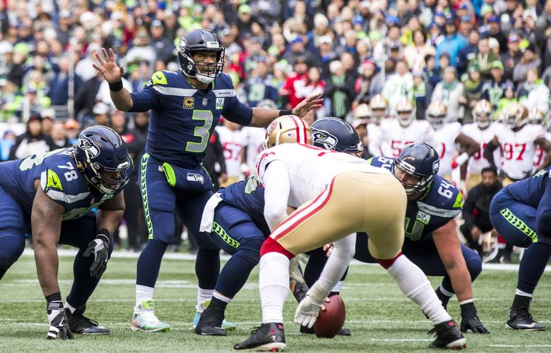 Seahawks quarterback Russell Wilson calls a play in the red zone in Seattle's 43-16 win over the San Francisco 49ers. (Bettina Hansen / The Seattle Times)