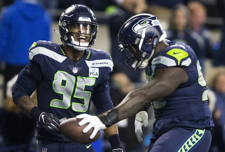 Seahawks defensive end Dion Jordan (95) and Seattle Seahawks defensive tackle Jarran Reed celebrate Sunday night against the Chiefs at CenturyLink Field. (Mike Siegel / The Seattle Times)