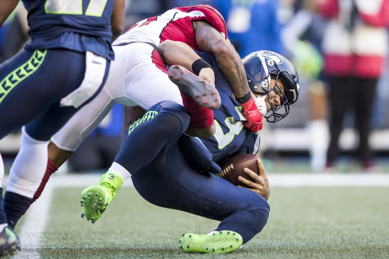 Seahawks quarterback Russell Wilson is sacked by Cardinals free safety Antoine Bethea in the first half as the Seattle Seahawks take on the Arizona Cardinals for the final game of the regular season at CenturyLink Field in Seattle, Sunday December 30, 2018.  (Bettina Hansen / The Seattle Times)