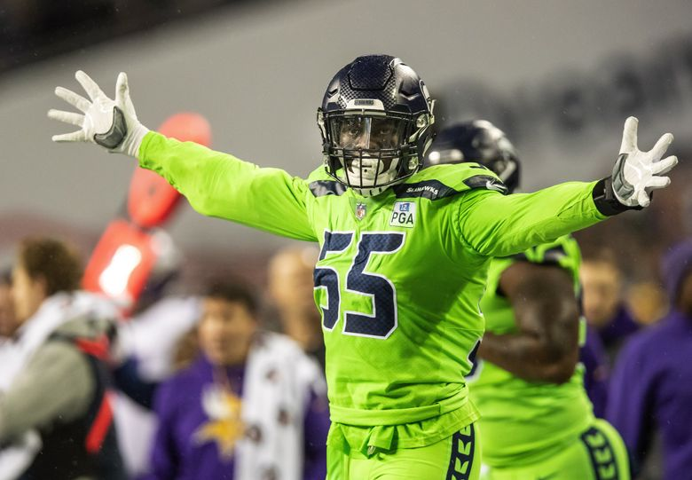 Frank Clark celebrates after flushing Minnesota quarterback Kirk Cousins from the pocket and tossing him out of bounds in the 2nd quarter. (Dean Rutz / The Seattle Times)