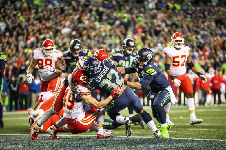 Russell Wilson comes in to help shove Chris Carson into the end zone on what would be the winning score in the fourth quarter against Kansas City. (Dean Rutz / The Seattle Times)