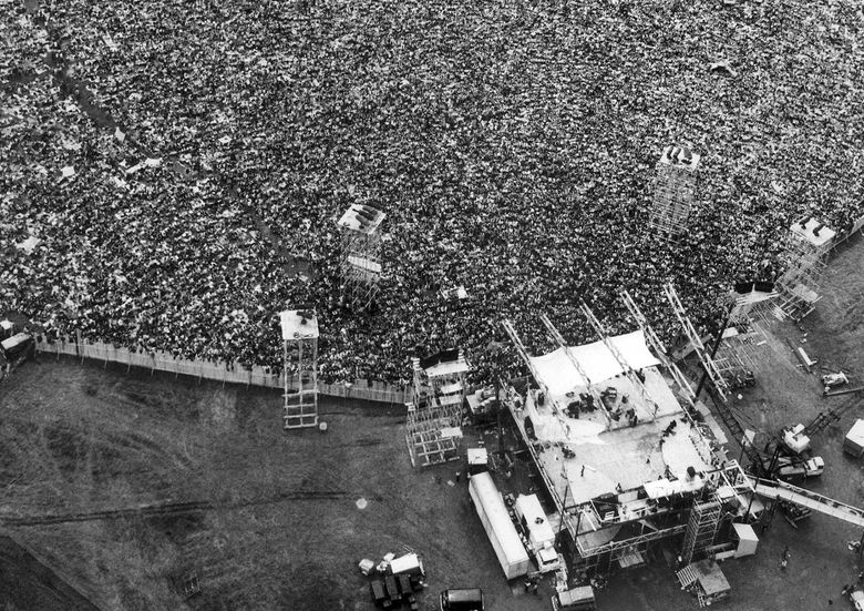 Music fans in 1969 pack around the stage at the original Woodstock Music and Arts Festival, lower right, in Bethel, N.Y. (AP Photo/Marty Lederhandler, file)